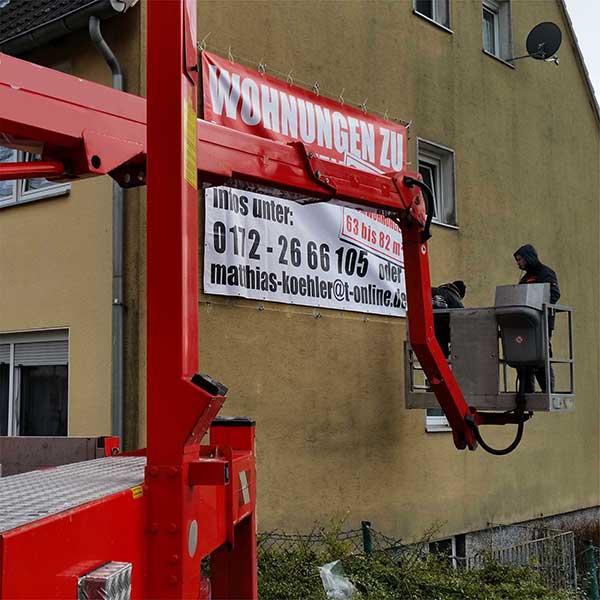 Hubwagen Montage PVC Frontlit Banner an Fassade - Werbekaiser™